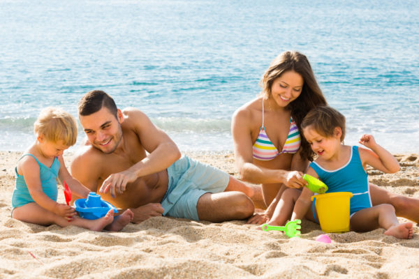 Happy smiling family of four playing with sand at beach in sunny day